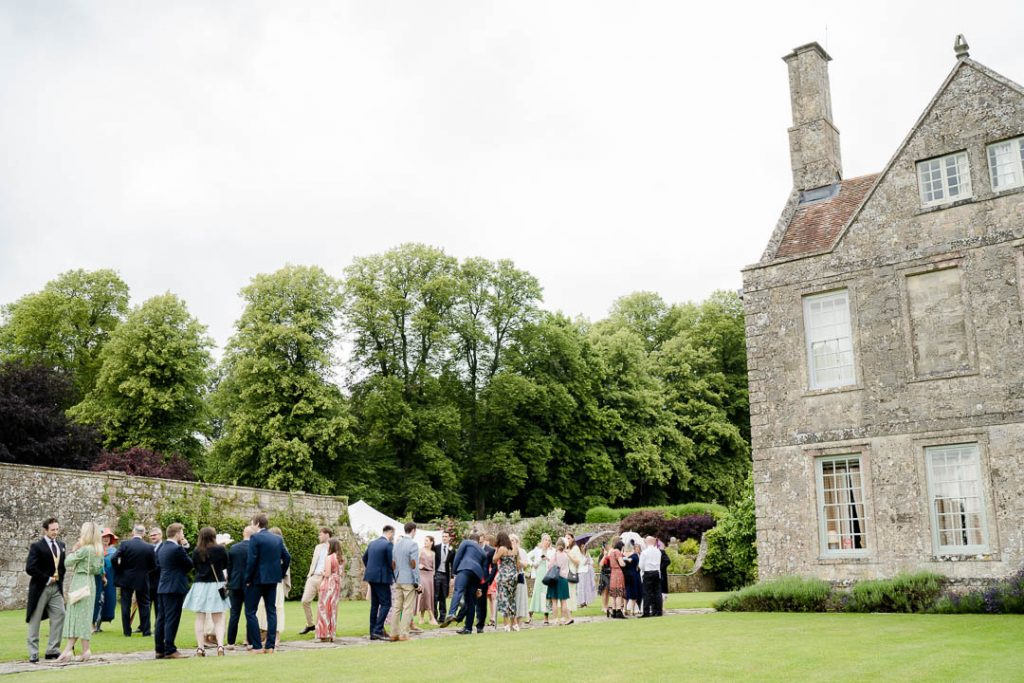 wedding guests gathering outside Hatch House wedding venue in Wiltshire photo by Lydia Stamps Photography