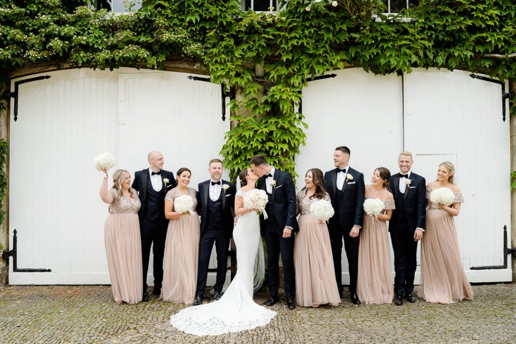 bride and groom and their wedding party outside the doors at Northbrook Park wedding venue near Farnham Hampshire photo by Lydia Stamps Photography