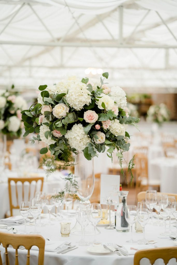 tall centrepieces featuring pink roses and white hydrangeas by Fiona Curry Flowers at Northbrook Park photo by Lydia Stamps Photography