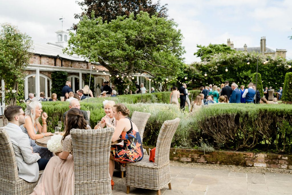 guests relaxing in the courtyard at Northbrook Park Hampshire during a drinks reception photo by Lydia Stamps Photography