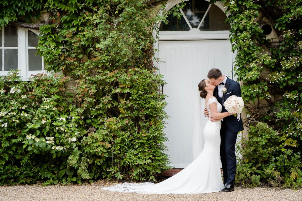 bride and groom kiss outside Northbrook Park Hampshire photo by Lydia Stamps Photography