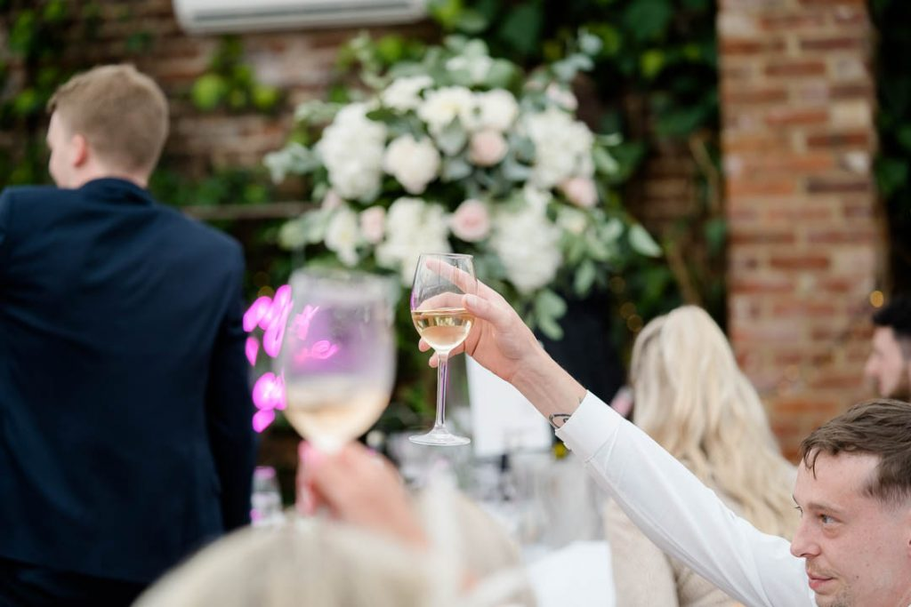 a glass is raised during a toast during wedding speeches in the orangery at Northbrook Park wedding venue in Hampshire photo by Lydia Stamps Photography